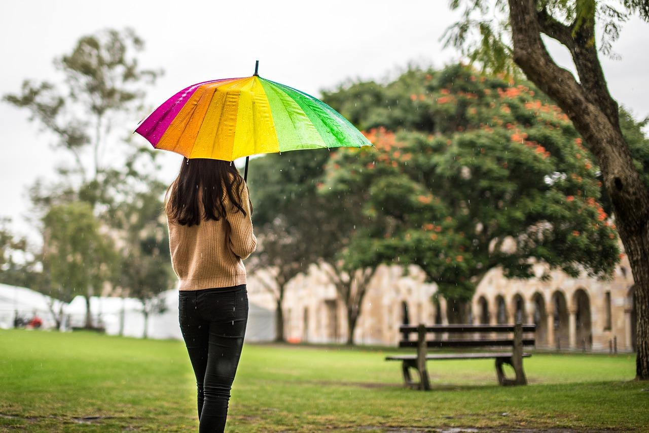 公園でひとり傘をさしてたたずむ女性