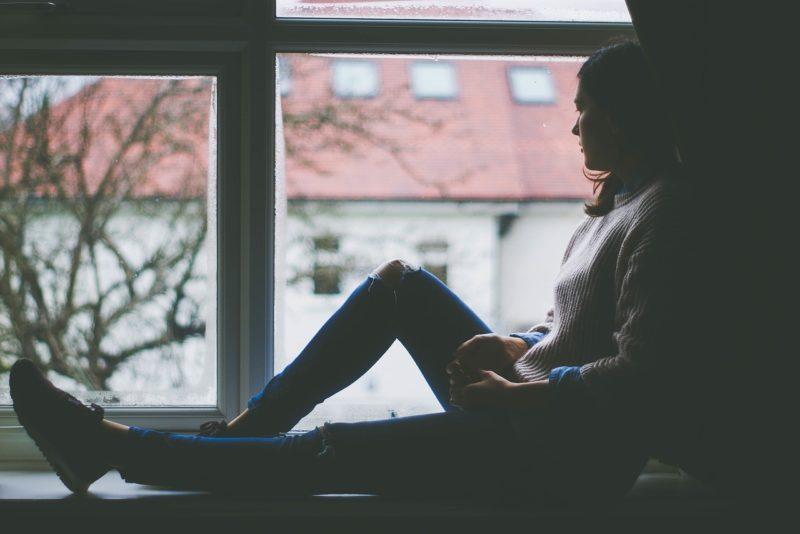窓の外を見る孤独な女性