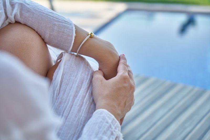 リゾートホテルのプールサイドで座る女性
