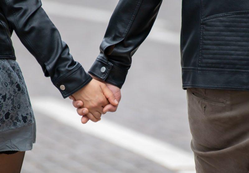 仲良く手を握りながら休日を楽しむカップル