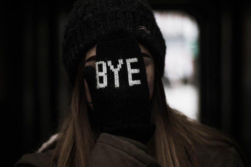 BYEと書かれた手袋で顔を覆う女性