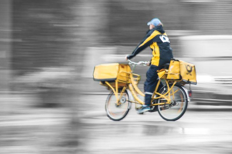 郵便配達の自転車に乗って配達に出るアルバイトの女性