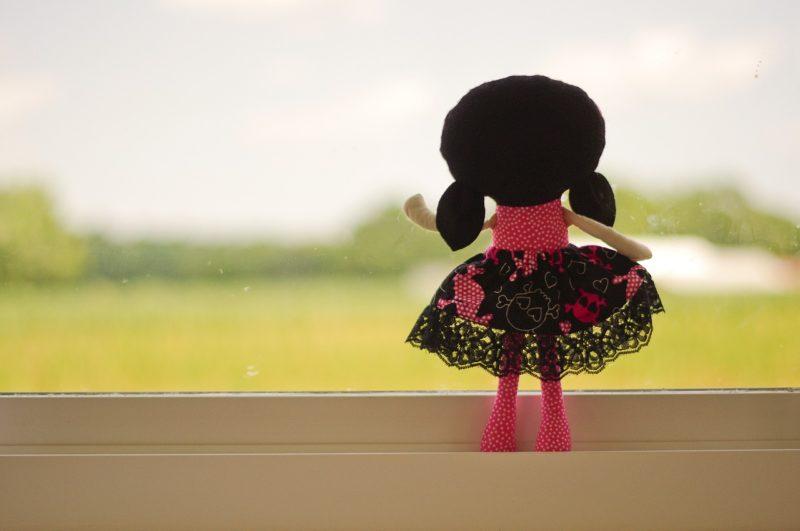 窓の外に向かい手を振りさようならをイメージさせる人形