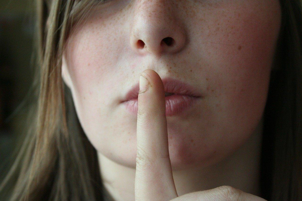 唇に人差し指を立て無言の仕草をする女性