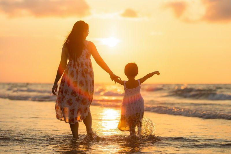 旅行先の海岸で夕陽をあびて手をつなぎ楽しそうにあるく母娘
