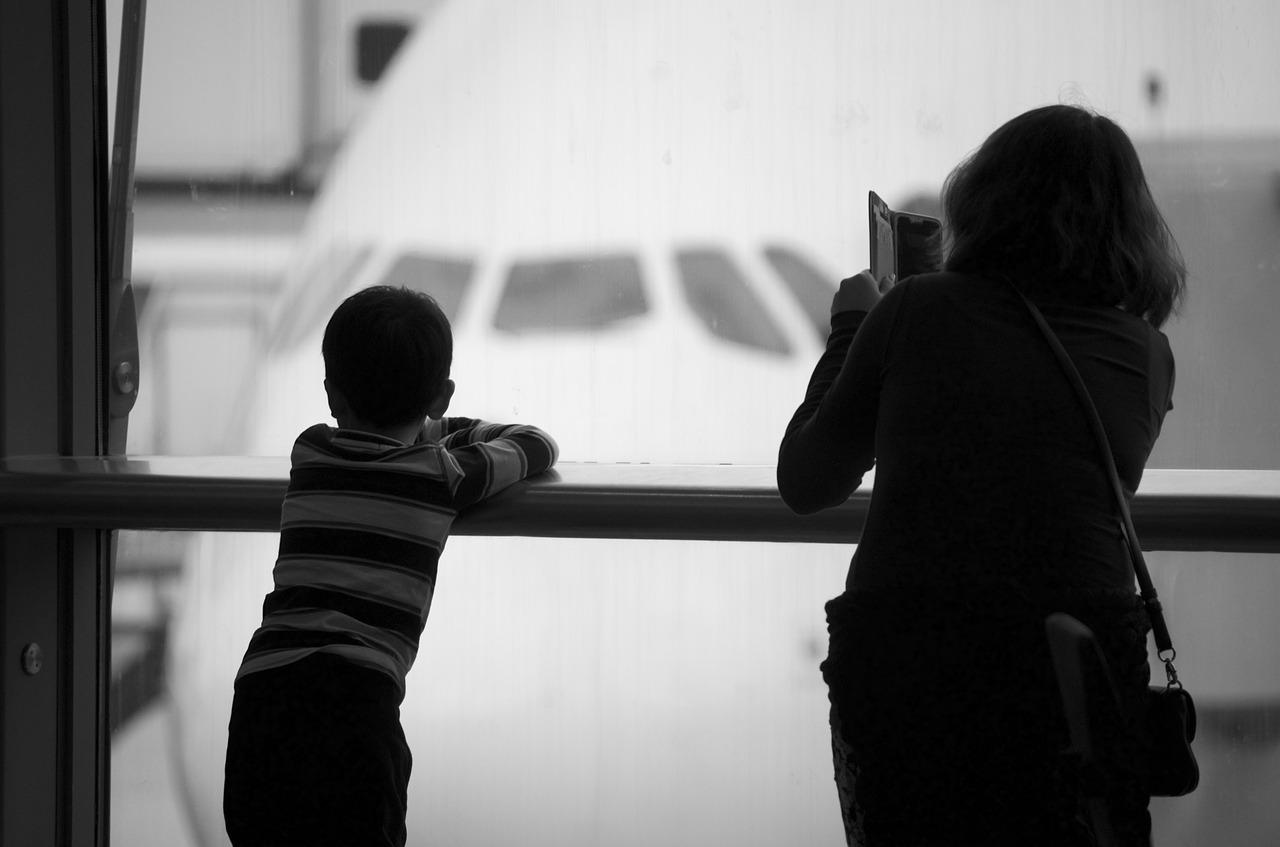 搭乗する飛行機をバックに孫の写真を撮る義母