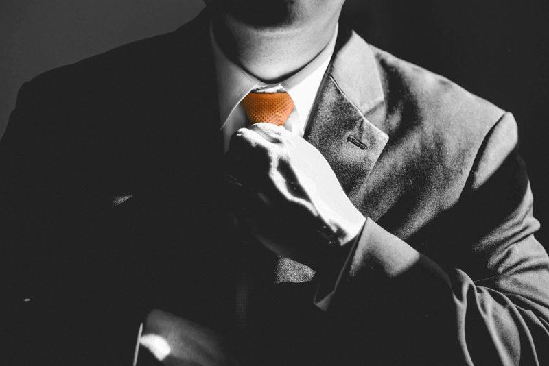 ネクタイを締め直し上司にお願いに向かう男性社員