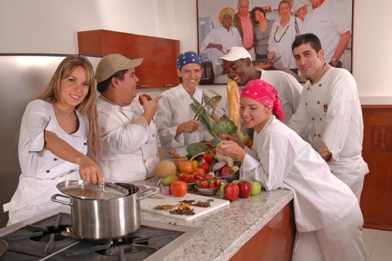 バイト先のレストランのキッチンで仲間と談笑する女性