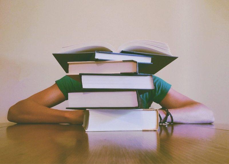 準備した教科書を高く積みそれに埋もれてしまった女子学生