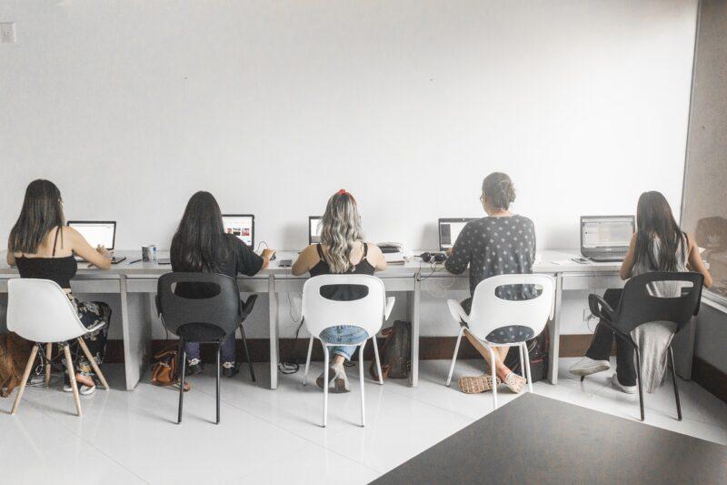 職場でPC仕事を前に仕事をする女性達