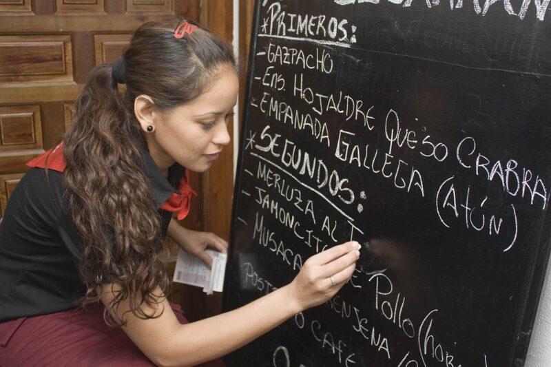本日のおすすめメニューを黒板に書く女性