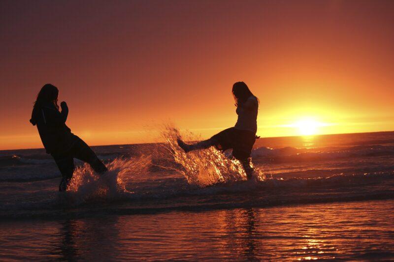 ビーチで夕陽を浴びながら友達と遊ぶ女性