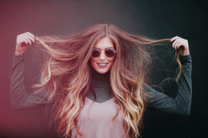 自分で自分のの髪を引っ張りおどけて見せる可愛い女の子